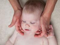 Младенца держат за шею
