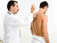 Врач обследует спину пациента