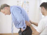 Врач обследует пациента с болью в пояснице