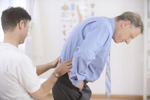 Врач осматривает спину пациента