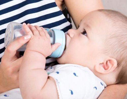 Младенец пьет из бутылочки