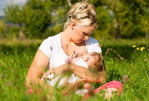 Мама кормит грудью на солнце
