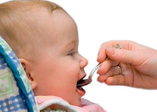 Малыша кормят с ложечки
