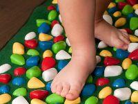 Ребенок стоит на ортопедическом коврике