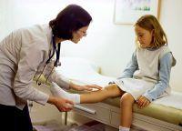 Доктор осматривает ногу ребенка
