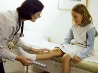 Врач осматривает колено у ребенка